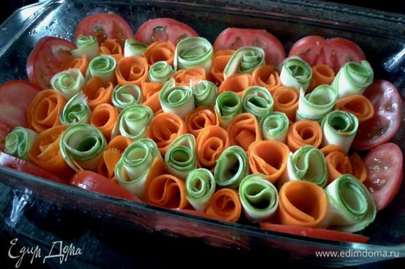 Кабачок и тыкву нарезать тонкими пластинками с помощью овощечистки. Помидоры нарезать кружочками. Смазать форму маслом (у меня стеклянная 30х20 см). Скрутить из овощных пластинок рулетики и установить их в форме в шахматном порядке, по бортикам установить дольки помидора.
