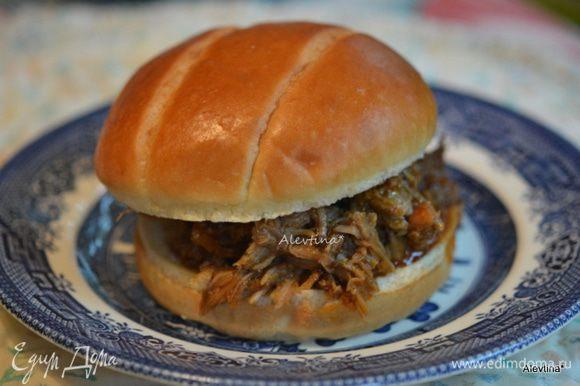 Готовую свинину очистить от лука. Размять вилкой на кусочки. Перемешать с соусом из медленноварки. И подавать с булочками для сэндвичей, например как бриоши. Приятного аппетита.