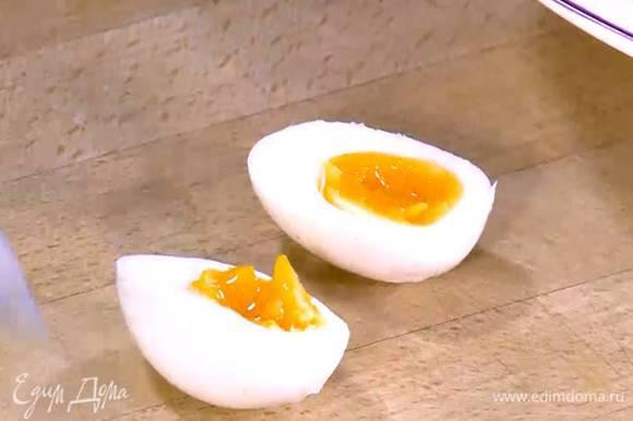 Яйца почистить, разрезать пополам и выложить на салат.