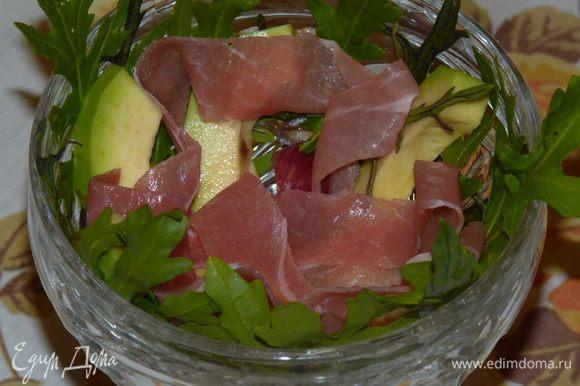 Выложить в салатники листки руколы, авокадо и хамон. Сбрызнуть заправкой.