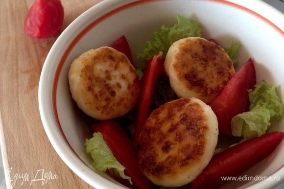 Затем в тарелки выложить сырники и полить заправкой. Посыпать зеленым луком, зеленью и подавать к столу.
