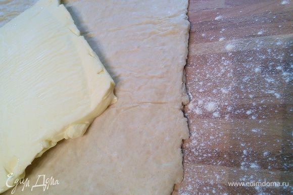 Поверхность присыпать слегка мукой, выложить тесто. Масло освободить от бумаги и выложить на пласт теста так, чтобы получить шестиконечную фигуру.