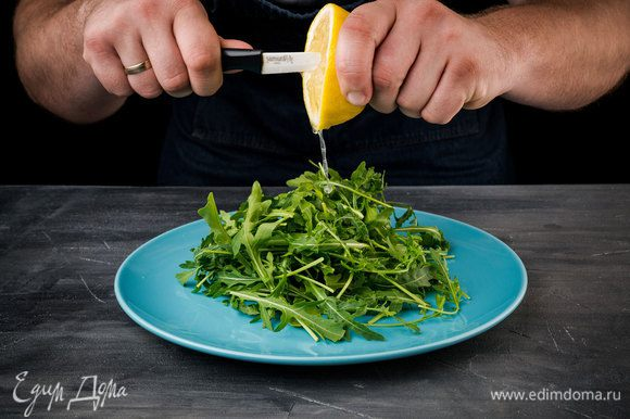 Выложите на тарелку, заранее вымытую и высушенную руколу. Немного сбрызните лимоном.