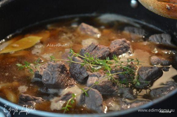 Вернуть мясо, добавить тимьян. Довести до кипения. Убавить огонь, закрыть крышкой и готовить 1 час. 15 мин.
