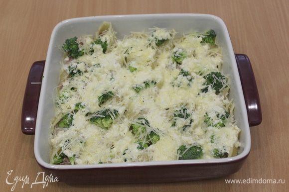 Полить ракушки сверху сырным соусом и присыпать отложенным тертым сыром.