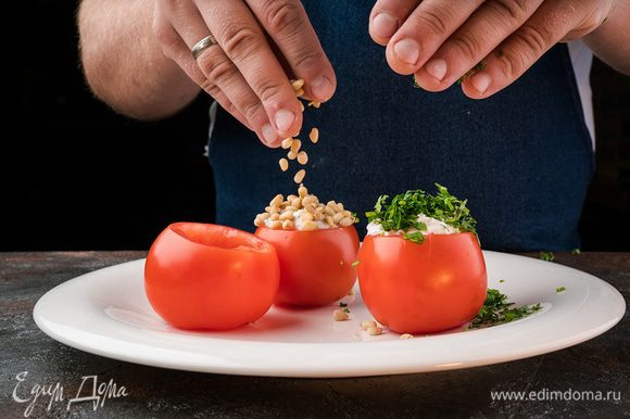 Наполнить помидоры начинкой, посыпать кедровыми орехами, кинзой.