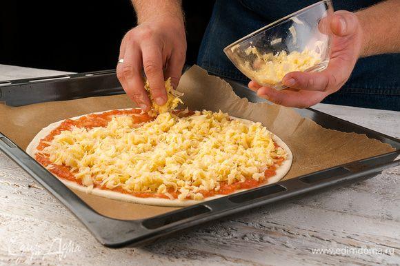 Потом посыпаем тертым сыром, сверху кладем нарезанную тонко колбасу, лук и перец. Отправляем пиццу в разогретую до 200°С духовку на 15 — 20 минут.