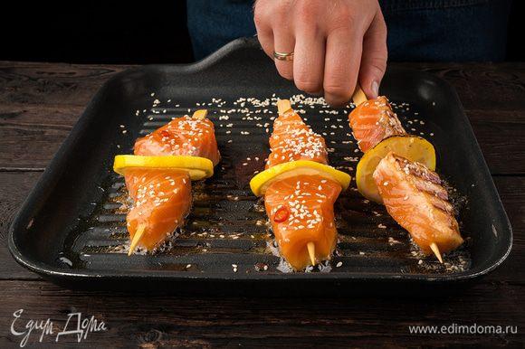 Лимон нарежьте тонкими кружочками. Нанизываем в таком порядке: кусочек лимона, затем рыбу и опять кусочек лимона. Обсыпаем рыбу кунжутными семечками. Жарим на сковороде-гриль 4–5 минут.