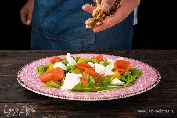 Апельсин, сыр и рыбу выложите сверху на руколу, еще раз сбрызните лимоном и добавьте немного масла. Посыпьте сверху салат грецкими орехами.