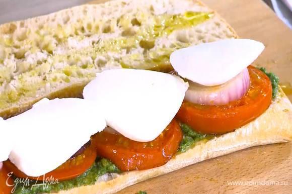 Чиабатту разрезать вдоль пополам и сбрызнуть оставшимся оливковым маслом, одну половину смазать соусом песто, выложить на нее обжаренные помидоры, лук и моцареллу.