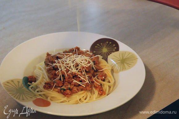 Приступаем к формированию отдельных порций. На дно тарелки кладем желаемое количество спагетти. Сверху выкладываем соус и посыпаем мелко натертым твердым сыром.