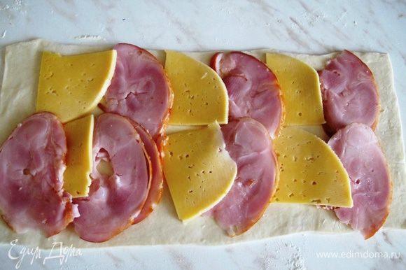На пласт теста выкладываем ветчину и сыр.