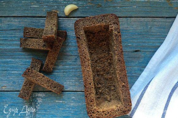 Разогрейте духовку до 100°С. Срежьте у буханок хлеба верхушки и аккуратно удалите мякиш, стараясь не повредить дно и стенки. Смажьте буханки изнутри чесноком и сливочным маслом и уберите в духовку на 15 минут.