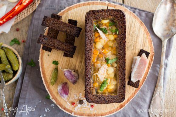 Разлейте суп в подсушенные буханки, украсьте зеленью и подавайте. Приятного аппетита.
