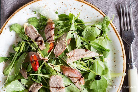 На тарелки выложите руколу, кресс-салат и шпинат, сбрызните соусом, затем выложите ломтики утиной грудки, посыпьте сверху кунжутом. Украсьте салат бальзамическим соусом и подавайте. Приятного аппетита!