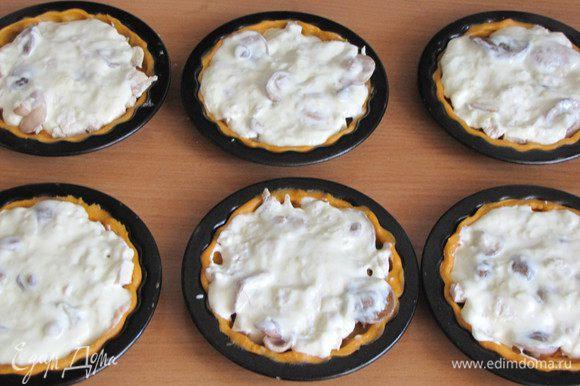 Сверху залить сырным соусом, равномерно распределить его. На одну тарталетку идет примерно 1,5 ст. л. сырного соуса.