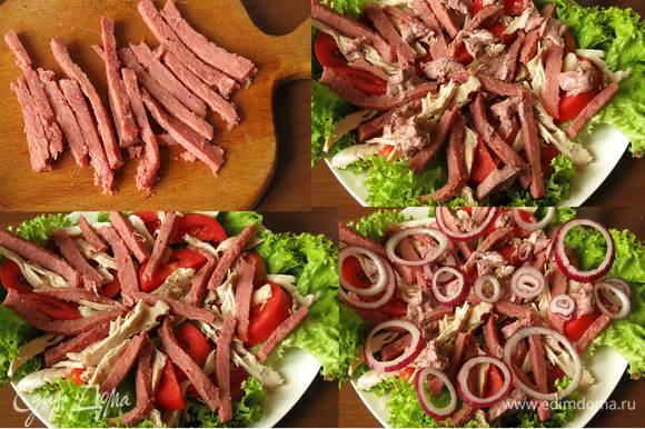 Нарезаем соломкой говядину. Выкладываем на томаты соломку. Кладем соус. Добавляем кольца лука салатного.