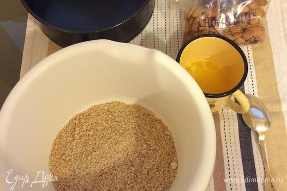Уменьшить температуру духовки до 170°С. В миске смешать молотое печенье и молотый миндаль. Добавить растопленное сливочное масло.