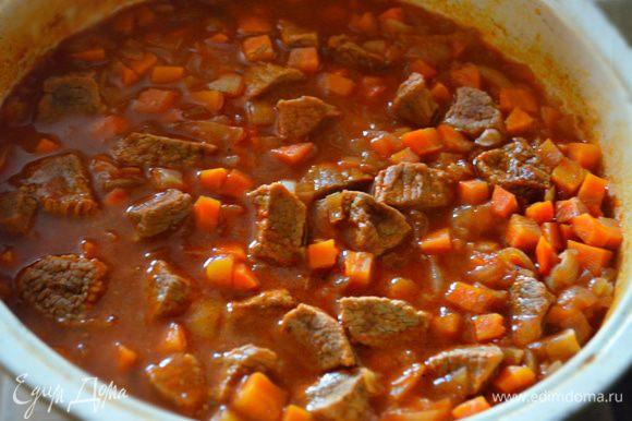 Мясо посолить, поперчить, добавить нарезанные лук и морковь, перемешать и тушить все вместе еще минут 20.