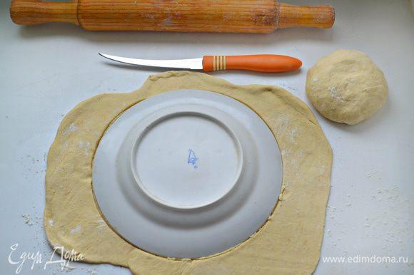 Тесто вынуть из холодильника, раскатать на пергаментной бумаге, слегка смазанной растительным маслом, и вырезать с помощью тарелки круг.