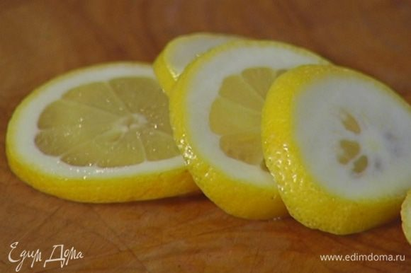 Половинку лимона нарезать тонкими кружками.