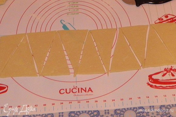 Раскатать тесто в пласт толщиной примерно 0,5 см. Тесто разделить на треугольники.