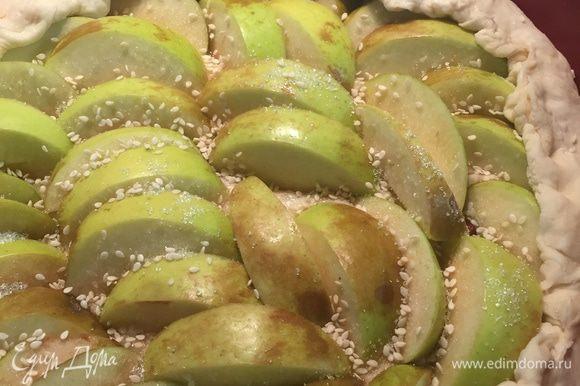 Уложить яблоки на тесто, завернуть краешки, присыпать сахаром и кунжутом.