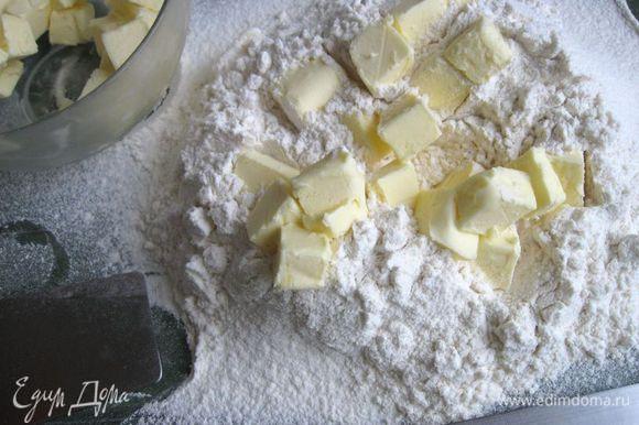 Достать масло из морозильной камеры, частями (в три приема) добавлять его к муке, рубить ножом, помогая себе лопаткой.