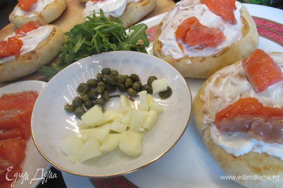 Выкладываем ломтики лосося, руколу, раскрошенный мягкий сыр (можно вместо моцареллы взять адыгейский, а лучше и тот, и другой), каперсы, солим, перчим.