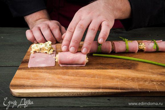 Ветчину нарезать тонкими слайсами по длинной стороне. На край каждого кусочка ветчины кладем начинку и сворачиваем рулетик. Стрелкой зеленого лука перевязать свиток.