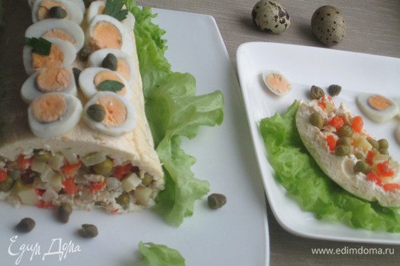 Переворачиваем салат на блюдо, освобождаем от пленки и начинаем украшать: яйцами, зеленью, каперсами.