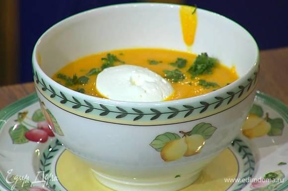 Суп разлить в тарелки, посыпать измельченной кинзой, в каждую тарелку выложить по ложке сметаны.