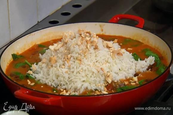 Мясо с овощами посыпать изюмом, выложить в центр сковороды готовый рис и посыпать все орехами.
