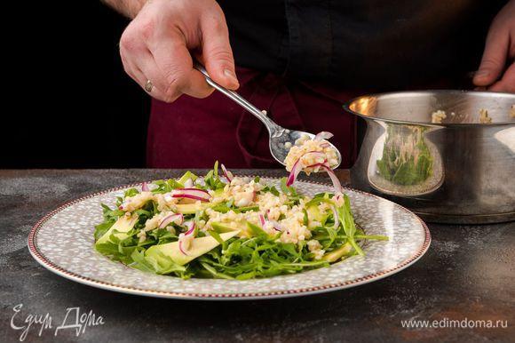 На блюдо выложить руколу, посолить, полить оставшимся лимонным соком и оливковым маслом, затем поперчить. Сверху разложить авокадо, булгур и зеленый горошек.