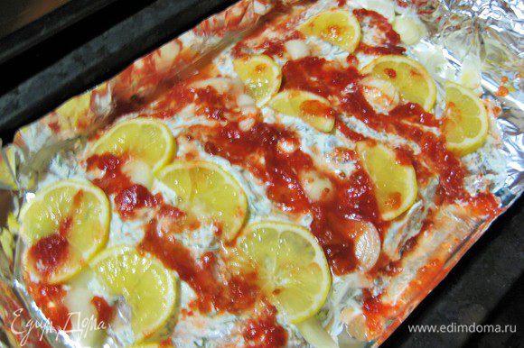 Сверху выкладываем дольки лимона, лук полукольцами, протертые помидоры в собственном соку. Запекаем в духовке 25 минут.