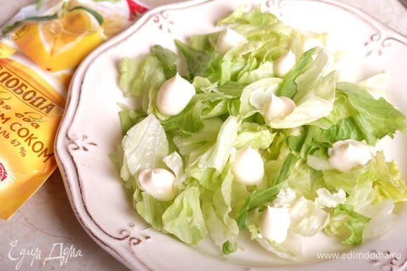 Собираем салат. На тарелку выкладываем щедрую горсть салата айсберг. Сверху — немного майонеза «Слобода» с лимонным соком.