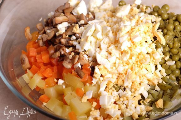 В миске соединить вместе: морковь, картофель, рубленые куриные яйца, горошек, нарезанные на мелкие кубики маринованные огурцы, обжаренные грибы и щепотку соли. Заправить постным майонезом ТМ «Слобода» и перемешать.