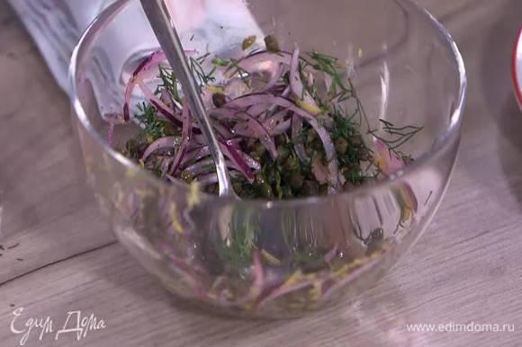 Нарезанный лук выложить в небольшую миску, добавить сок и цедру лимона, каперсы, укроп, поперчить, все перемешать и дать постоять.