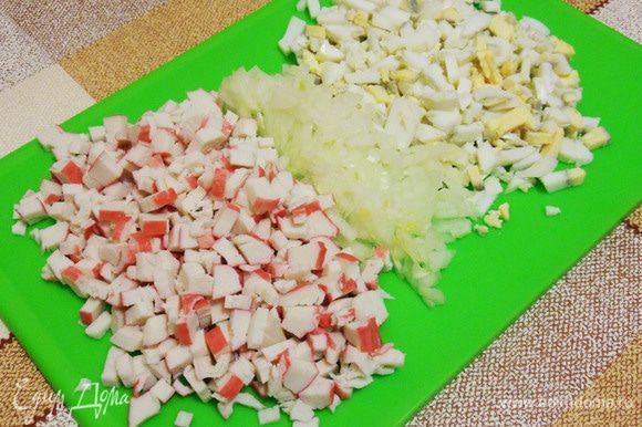 Кубиками нарезать лук, крабовые палочки, яйца.