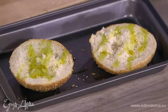 Булочки разрезать вдоль пополам, сбрызнуть оставшимся оливковым маслом и запечь под разогретым грилем.