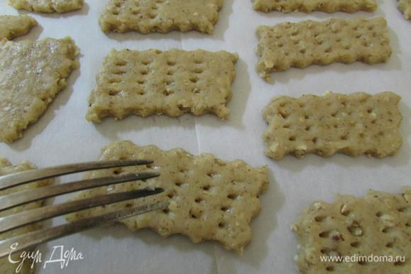 Противень застелить пекарской бумагой. Печенье выложить на подготовленный противень. И наколоть каждый крекер вилкой. Отправить в разогретую духовку до 160°С. Выпекать 12 — 15 минут.