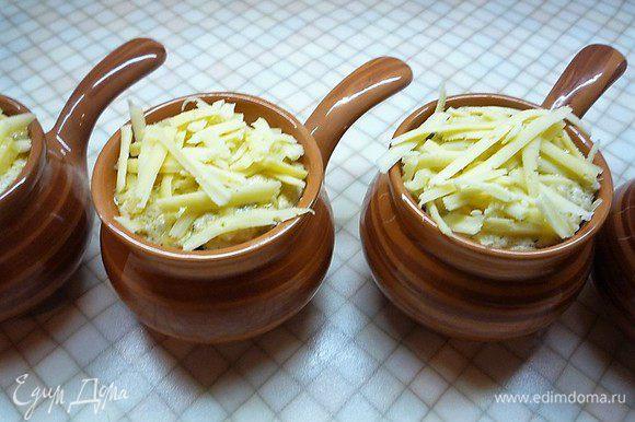 Сверху посыпаем тертым сыром. Ставим кокотницы в холодную духовку, выставляем температуру 180°С и запекаем пока сыр не расплавится и корочка не станет золотистой, примерно 15 — 20 минут.