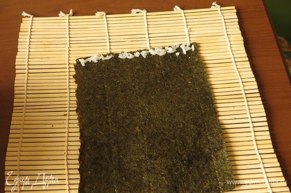 3/4 листа нори кладем на коврик (размер листа зависит от длины яичного рулета). По краю листа выкладываем тонкой полоской рис.
