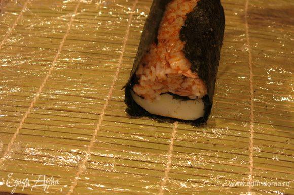 Поднимаем листы нори от края к центру, так, чтобы сохранить положение цветного риса над кальмаром, внутри получается фигура овал.