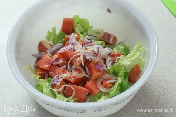 Листья салата рвем руками. Добавляем кусочки рыбы, нарезанный красный лук.