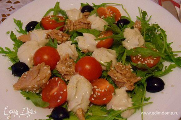 Выложить салат на тарелки. Сверху уложить кусочки тунца, чайной ложкой полить соусом. Присыпать для украшения кунжутом. Можно добавить половинки маслин.