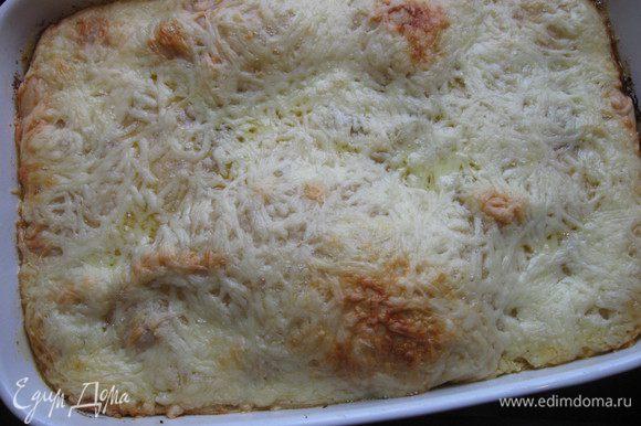 Верхним слоем является тесто, которое следует посыпать натертым сыром эмменталь или гауда (я терла на крупной терке, можно и на мелкой). Сверху распределить кусочки сливочного масла. Поставить форму с пирогом на 40 минут в духовку. Если верхний слой начнет становиться коричневатым, накройте пирог пекарской бумагой. Вынуть пирог из духовки.