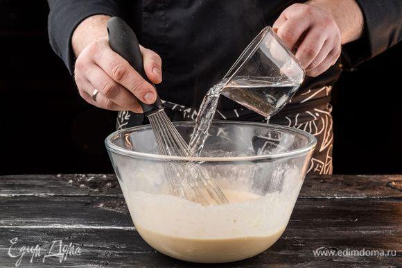 Непрерывно перемешивая тесто венчиком, влить стакан крутого кипятка.