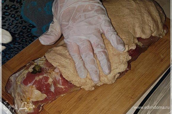 И обмазываем мясо тестом. Заключаем, значит, его, мясо, в калитку. Сначала с одной стороны.