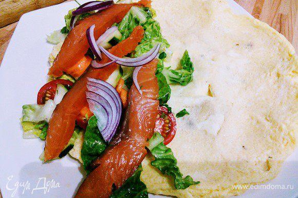 Выкладываем омлет на тарелку, на одну сторону выкладываем салат и кусочки лосося (рыбка тоже может быть любая).
